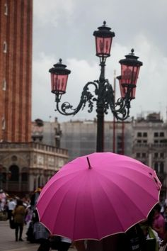 A colorful pink umbrella brightens a dreary day.