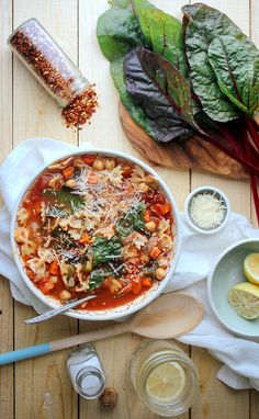 Chickpea Tomato Minestrone: 1 Tablespoon olive oil 1 medium onion, chopped 2 celery stalks, chopped 2 carrots, chopped 3 garlic cloves, minced 2 Tablespoons tomato paste 1 can of diced tomatoes 4 cups vegetable broth 1/2 teaspoon dried oregeno 1 cup of pasta  1 can chickpeas, 1 bunch of swiss chard, Salt / Pepper Dash of Red Pepper flakes Parmesan, for garnish