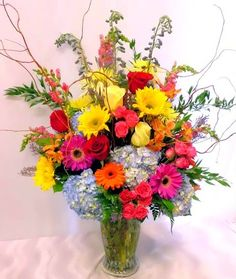 A sumptuous array of the very best in seasonally fresh flowers. An abundance of hydrangea, roses, spray roses, alstroemeria, gerbera daisies, hydrangea, and snaps are arranged along with seasonal greens and curly willow. The piece is beautifully presented in a classic twisted vase. For local delivery only.