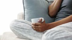 Mixed race woman on sofa using cell phone and drinking coffee Stock Footage
