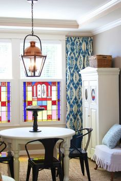Dining room with blue and white ikat curtains and a copper lantern
