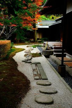 Gravel walk with round and rectangular stepping stones leading to tea room make this Japanese garden special.