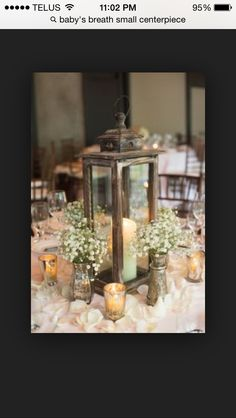 The lantern is lovely, maybe we could find in gold or spray paint? This would also require very little baby's breath blooms and use the tea lights provided by venue.