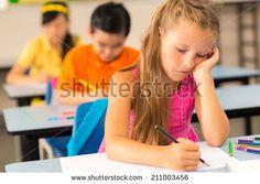 Tired little schoolgirl drawing in classroom