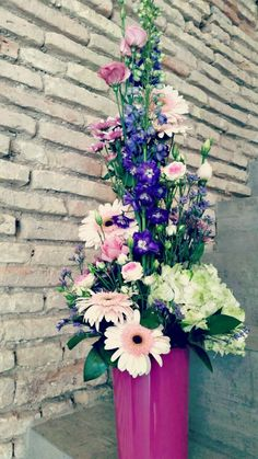 Vertical floral arrangement in purple and pink with pink ceramic vase