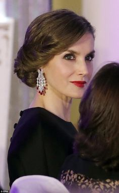Striking: She completed her glamorous look with a striking pair of chandelier earrings, and a slick of shimmery red lipstick