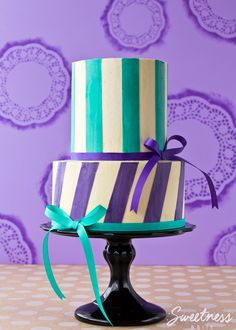 Step by step tutorial on using waxed paper to create perfect buttercream stripes. Part 1 details covering the cake with buttercream to create straight sides