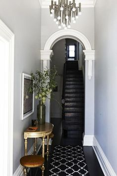 Chic entryway with gray walls, a black staircase, a rug, and a eclectic chandelier