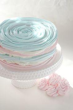 Pastel hecho con ruedas de merengue de colores,apilados y rellenos de crema con fresas