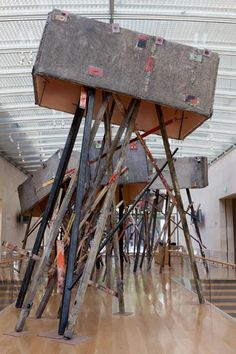 Phyllida Barlow Grey crates with splashes of pink, red, black and green are propped up on lumber stilts