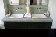 A perfectly smooth counter material is less important in a bath than it is in a kitchen so why not use tile?