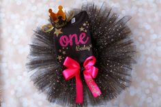 Beautiful Black Gold and Pink Coordinating Personalized First Birthday set including black bodysuit, gold twinkle twinkle little stars with pink number one in script and baby's name. Set comes complete with personalized baby crown and black and gold tutu with satin ribbon. This set is completely customizable in the colors.