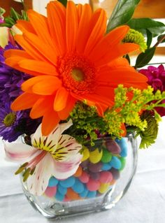BRIGHT flowers in a vase with jelly beans. Just place a smaller vase inside the large one, to be able to water your flowers.