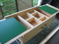This is a Lego Table that has a sliding top to expose a storage area. The legs fold under and has a handle for carrying. Solis Pine with plywood top and base.