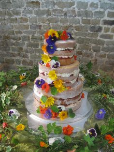 a 3 tier rustic wedding cake with edible flowers