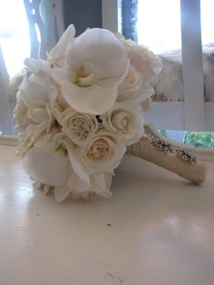 White roses and Orchids Bouquet.  I would have pearls wrapped around it instead of ribbon.