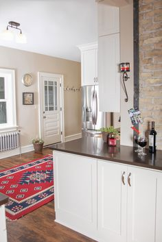 Transitional kitchen white painted cabinetry with Caesarstone countertop tops. Stainless steel appliances and hardwood flooring. Farm house sink