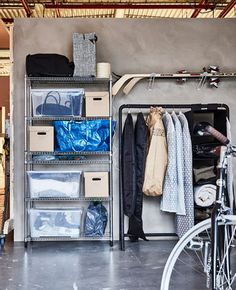 Winter sports gear and clothing are stored in plastic and paper boxes, sturdy plastic bags, and on racks in a garage.