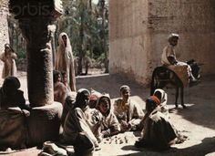 Children play a game outside in the Tozeur oasis.  1924.  Tozeur, Tunisia.  © Gervais Courtellemont/National Geographic Society