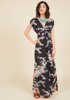 <p>Glide through your day feeling dreamy as can be in this printed maxi dress! An ethereal print of illustrated bouquets and stunning peacocks adorns the soft black silhouette of this V-necked, short-sleeved frock, creating a look that is both vibrant and poised. </p>