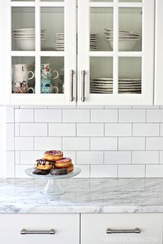 White subway tile as back splash. Silver grout. Name of tiles in article.