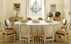 adore this dining room with its large linen covered skirted table.  But the antique leather French chairs make such a huge statement here.