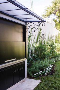 El jardín de esta casa tiene parrilla con un sistema de cierre tipo guillotina, techo y piso de baldosas para evitar que las brasas arruinen el pasto.