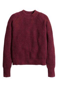 Ribgebreide trui: Een zachte, ribgebreide trui met wol. De trui heeft een brede ribgebreide halsboord en lange raglanmouwen.