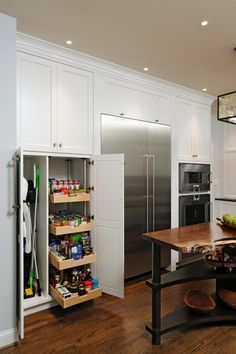 Pull-out pantry doors are cleverly hidden behind white cabinets in this cheerful kitchen. Integrated appliances include a steam oven and warming drawer. At the center of the space, a custom island features a unique live-edge walnut top.