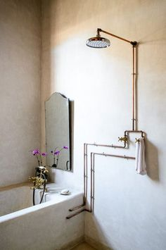 Love the copper shower pipes and giant shower head in this wet room