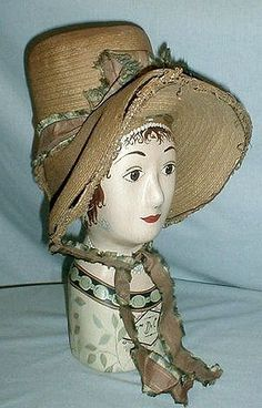 1820-1830 tall crown straw bonnet that has recently been de-accessioned from a museum collection. The cataloging number is stitched inside the bonnet. The bonnet has a full wide brim that is accented with decorative straw braiding. The bonnet still retains its original tan and green silk ribbon trim and chin ties