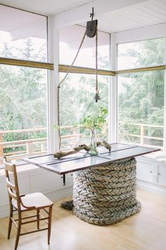 Sloping rope, up, over and down, gives design to the high ceiling space.  Easy to find a pulley at a garage sale.  The single bulb could be shaded.   The table is a door -  sitting on heavy braided wound cable.   5 Quick Fixes: Repurposed Doors as Decor : Remodelista