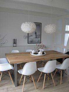 chaises en plastique blanc, table en bois clair, lustre boule blanc, sol en parquet clair:
