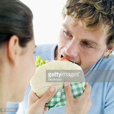 Foto de stock : Close-up of a young woman feeding a young man a pita bread sandwich