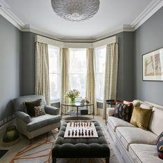Grey living room with bay window and floor-length curtains