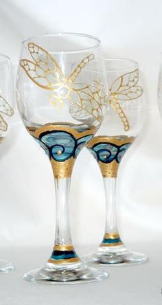 Art on Glass hand painted whimsy in mini wine glass cordials in a set of four. Individually designed and hand painted with a unique swirling opalescent blue waves. Shimmering faux gold surround the op