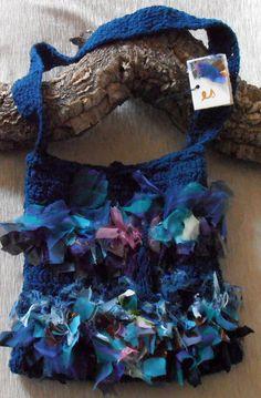 borsa di cotone a tracolla melange color blu-verde, realizzata a uncinetto e decorata con nastri di tessuti pregiati tagliati a vivo e annodati uno...