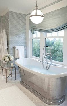 Lovely gray bathroom. Beautiful tile, tub and pendant.