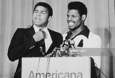 American boxers Muhammad Ali (left) and Leon Spinks smiling at a podium at a press conference at the Americana Hotel to announce their upcoming fight, New Orleans, Louisiana. Leon Spinks, Larry Holmes, Muhammad Ali Boxing, American Boxer, Bill Russell, American Games, Hometown Heroes, Boxing Champions, Summer Olympics