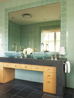 This unique vanity is modeled after a Parsons table and features an 8-foot-long slab of concrete that protects the maple-veneer cabinetry below from water splashes. Two glass vessel sinks lighten the look and repeat the soft, watery tones of the glass tiles that adorn the walls. Above the vanity, a large mirror framed in decorative tiles visually expands the room and enhances the bathroom's geometric feel./