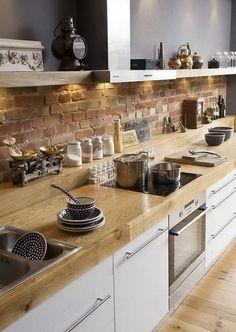 Biela kuchyna s drevenou doskou a tehlovym obklado...