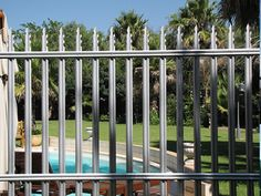 Gray steel palisade fence around the swimming pool, one pointed top type with…