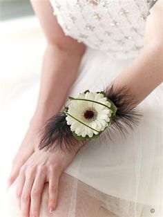 White Gerbera and Feather Wrist Corsage. We've chosen a stunning white germini as the centrepiece for this modern wrist corsage. Delicate black feathers, rich green leaves and fine strands of bear grass are carefully added to create a truly beautiful adornment.
