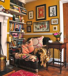 A cozy reading nook filled with a comfy chair, good books, and framed art.