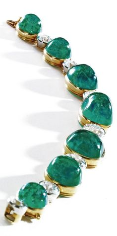 An Art Deco cabochon emerald and diamond bracelet, Cartier, New York, 1923. Cabochon emeralds weighing approximately 70.00 carats, old European-cut diamonds weighing approximately 9.50 carats, mounted in 18 karat gold and platinum, engraved on two separate collets London and England, on another collet numbered. #Cartier #ArtDeco #bracelet