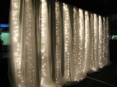 White Christmas lights behind sheer covered curtains is an expensive yet clever way to cover walls and create a nice ambiance in the room. Great idea for a room divider as well.