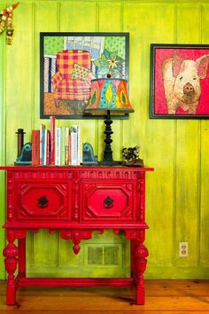 The red dresser pops against the green wall.