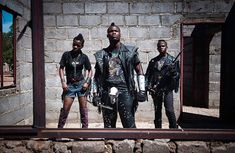 Edith, Hellrider, and Dadmonster pose for a photograph. In Botswana, heavy metal music has landed. Metal groups are now performing in nightclubs, concerts, festivals. The ranks of their fans have expanded dramatically. These fans wear black leather pants and jackets, studded belts, boots and cowboy hats. On their t-shirts stand out skulls, obscenities, historical covers of hard-rock groups popular in the seventies and eighties, such as Iron Maiden, Metallica, and AC/DC.