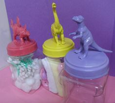 Buy plastic containers and cheap dinosaurs, hot glue the dinosaurs to the top of the lid, then paint with matching party colors.