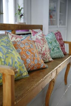 Pillows on a wooden bench - beautiful pattern and color. These would be cute on my window seat.